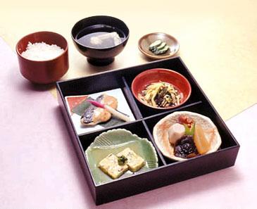 2002年3月9日−24日に国立劇場で上演された歌舞伎の演目にちなみ、期間中、国立劇場第1食堂の特別メニューとなった「江戸の弥生弁当」。(左上から時計回りに)目鯛くるみみそつけ焼き、和えまぜ、煮物(里芋、椎茸、大根、蛸のやわらか煮)、ぎせい豆腐といったおかずに、ご飯、汁(カモ、セリ、ゆば)、キュウリのぬかみそ漬けが付いている