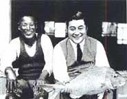 写真右が1929(昭和4)年当時の渋沢敬三(1896−1963)氏。本牧沖にて釣り上げた鯛と<写真提供:渋沢史料館>