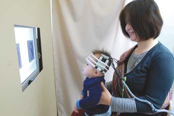 目から入った情報を認識する際の脳の働きを調べる実験。赤ちゃんの頭に光を当て、脳から反射される光の量を計測する