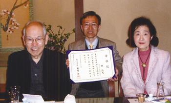 笑いと遺伝子に関する論文が認められ博士の学位を授与された「心と遺伝子研究会」林隆志研究員(中央)との一枚〈写真提供:村上和雄氏〉