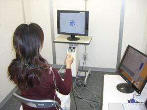 「注意」と「不注意」に関する実験の一つ。視覚的な課題を行なっている時に無関係な音声刺激が流れると、視覚課題に対する注意力が落ちることを脳波で検証した<写真提供:芳賀 繁氏>